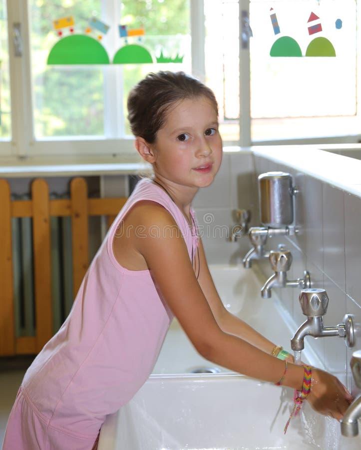 Mani di lavaggio della bambina nel lavandino ceramico nel bagno fotografie stock libere da diritti