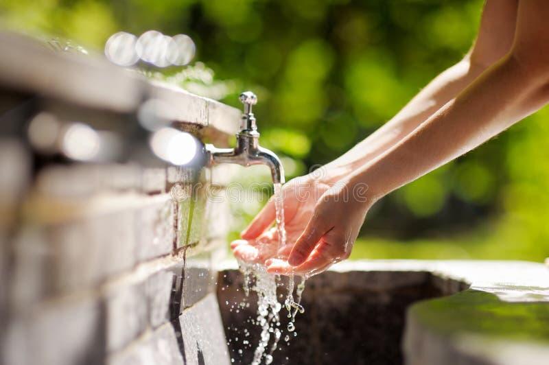Mani di lavaggio della donna in una fontana della città immagini stock