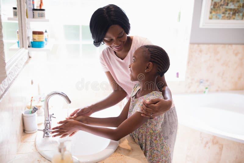 Mani di lavaggio della figlia e della madre al lavandino in bagno immagini stock