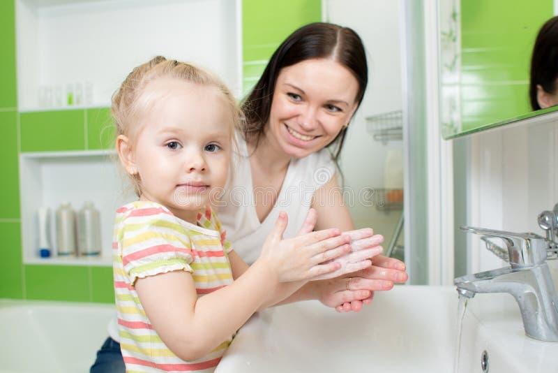 Mani di lavaggio della ragazza del bambino con sapone in bagno immagine stock libera da diritti