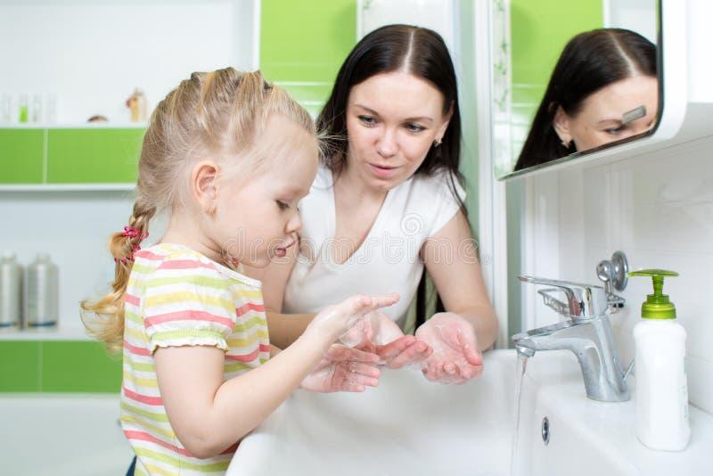 Mani di lavaggio della ragazza e della madre del bambino con sapone in bagno fotografie stock libere da diritti