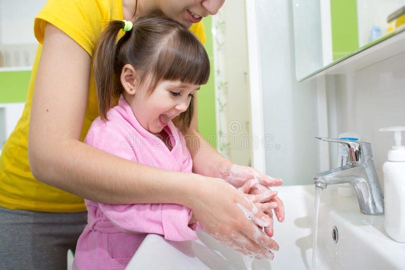 Mani di lavaggio della ragazza e della madre del bambino con sapone in bagno fotografie stock
