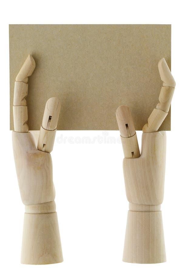 Mani di legno che tengono un pezzo di carta marrone in bianco immagini stock libere da diritti