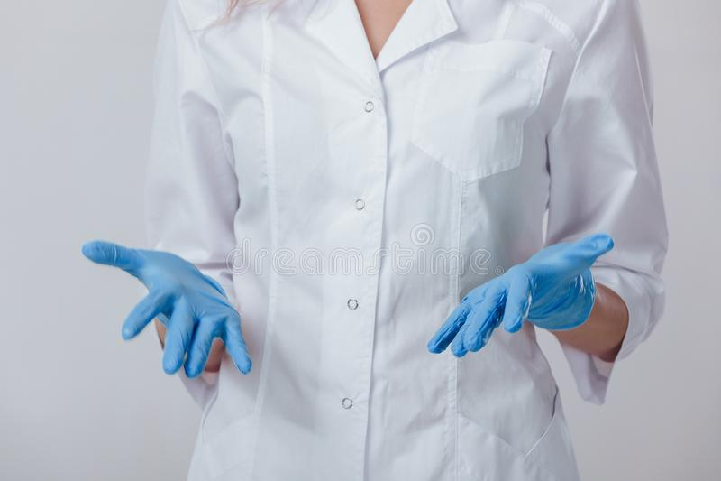 Mani di medico della donna nei guanti blu del lattice medico immagine stock libera da diritti