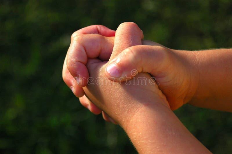 Mani di preghiera del bambino fotografia stock