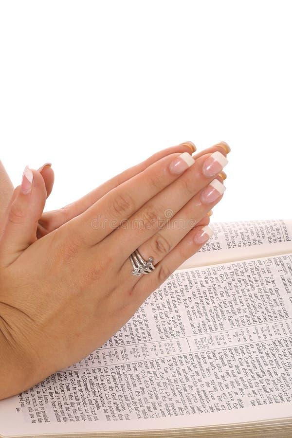 Mani di preghiera sulla bibbia fotografie stock