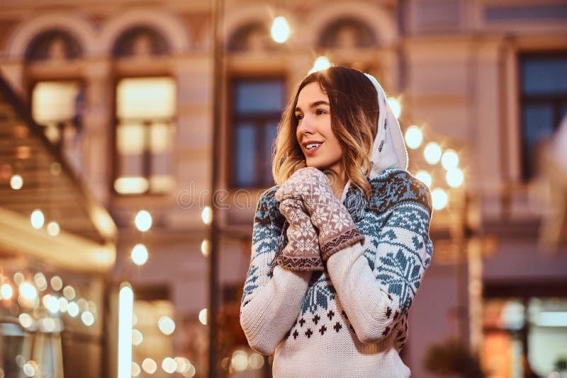 Mani di riscaldamento d'uso di un maglione della giovane ragazza affascinante in guanti tricottati, stanti nell'uguagliare via de fotografie stock