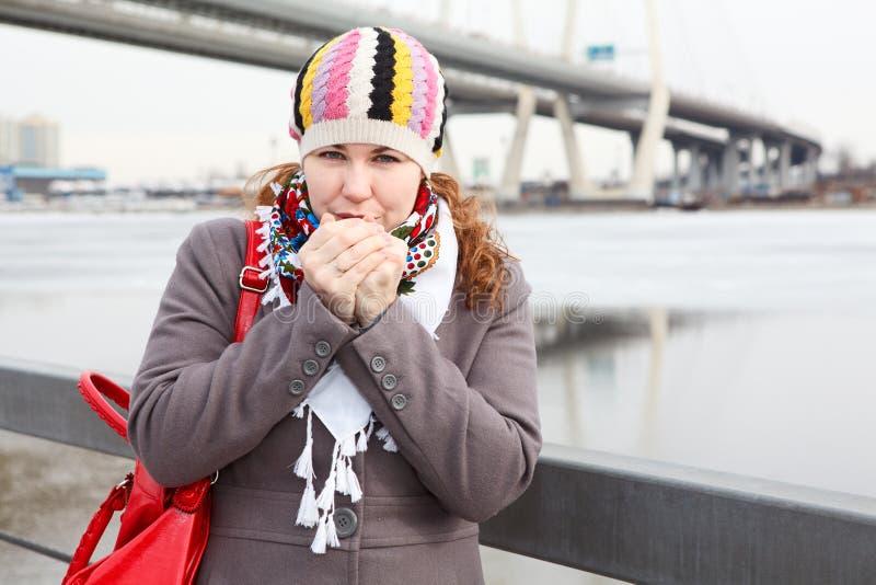 Mani di riscaldamento della donna nel freddo fotografia stock