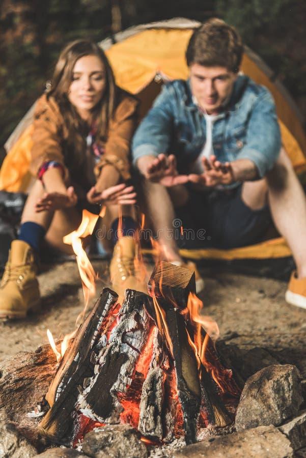 mani di riscaldamento delle coppie con il falò fotografie stock