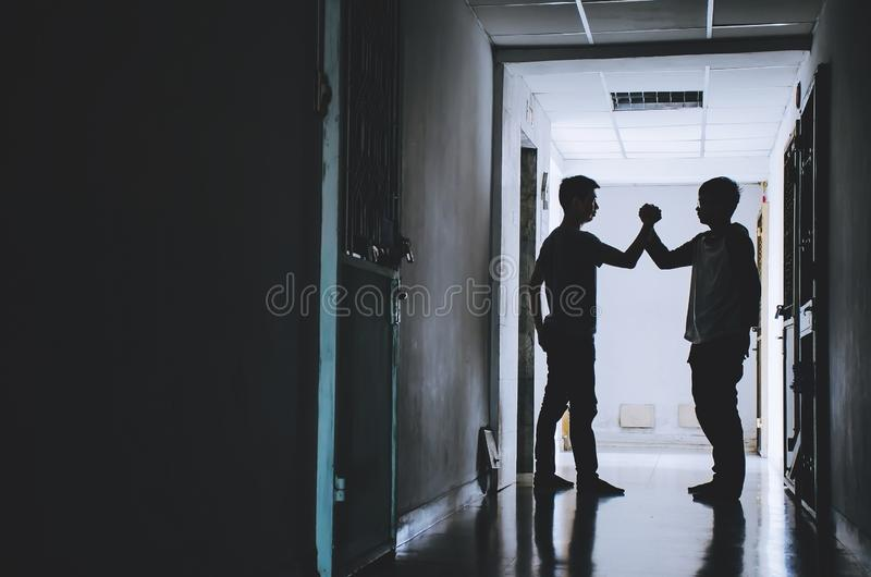 Mani di scossa dell'amico della siluetta due che finiscono un affare in mezzo dell'amicizia di successo e felice immagine stock