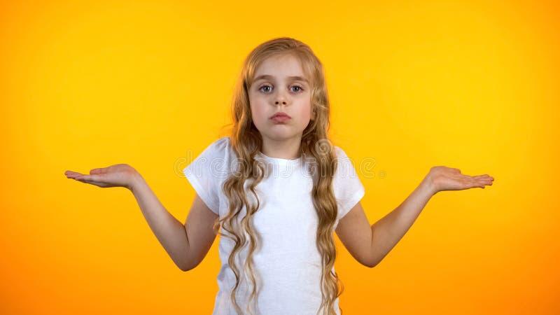 Mani di sollevamento della ragazza preteen incerta nella costernazione isolate su fondo giallo fotografia stock