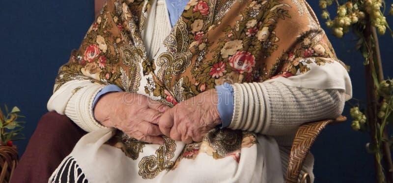 Mani di un'anziana ammalata rugosa seduta su una sedia fotografia stock libera da diritti