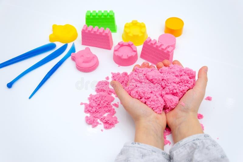 Mani di un bambino che gioca con la sabbia magica rosa fotografie stock