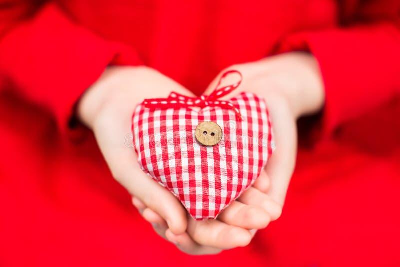 Mani di un bambino che tiene un cuore bianco rosso del tessuto del plaid con il bottone fotografia stock