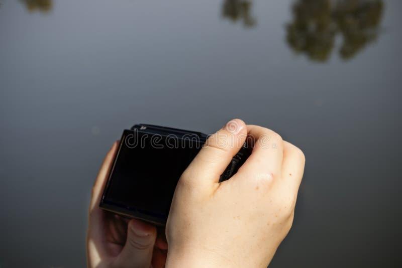 Mani di un bambino che tiene una macchina fotografica immagine stock