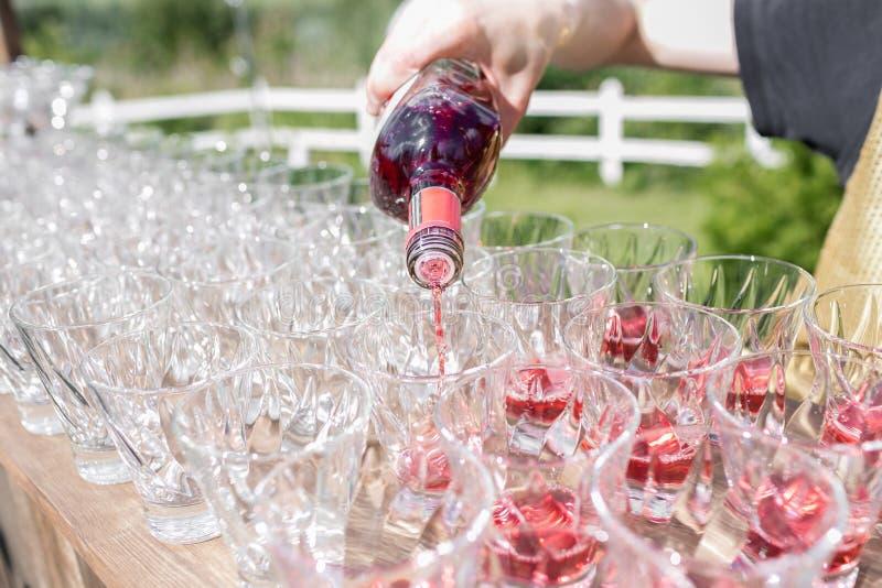 Mani di un cameriere che distingue la piramide dai vetri per le bevande, il vino, champagne, umore festivo, celebrazione fotografie stock libere da diritti