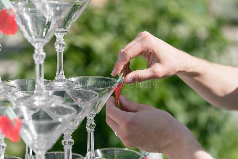 Mani di un cameriere che distingue la piramide dai vetri per le bevande, il vino, champagne, umore festivo, celebrazione immagine stock libera da diritti