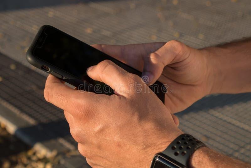 Mani di un giovane facendo uso del suo smartphone sull'esterno È il tramonto immagini stock