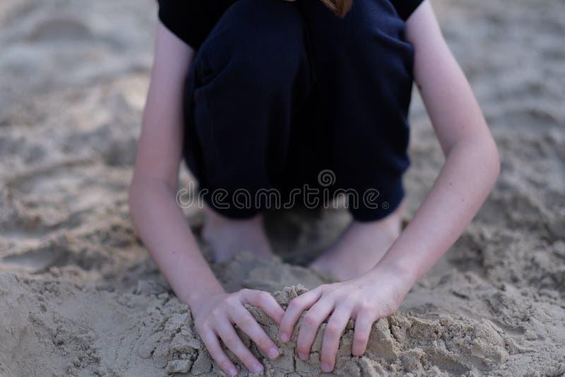 Mani di un ragazzo che gioca nella sabbia bagnata fotografie stock libere da diritti