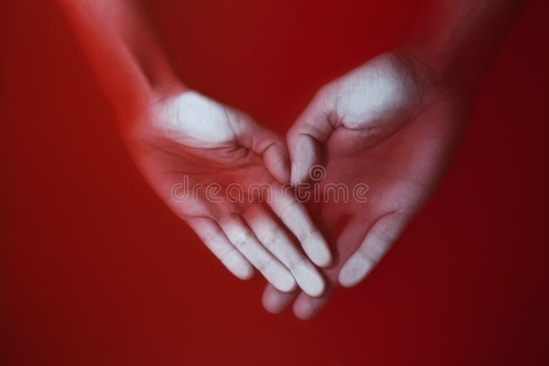 Mani di un uomo e di una donna sotto forma di un cuore che viene meno nell'acqua sanguinosa, nel concetto di amore e nel dolore fotografia stock