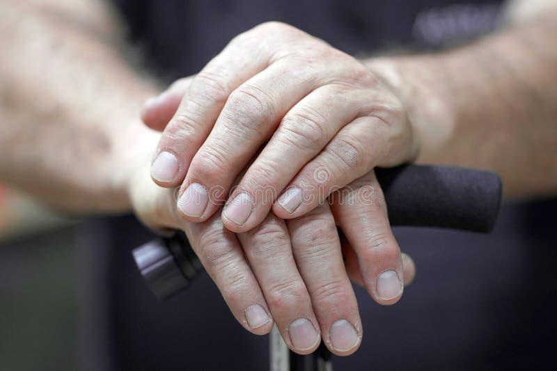 Mani di un uomo senior che tiene una canna immagine stock