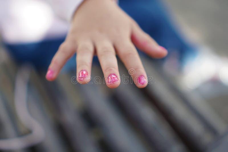 mani di una bambina che ha dipinto le sue unghie da solo immagine stock libera da diritti