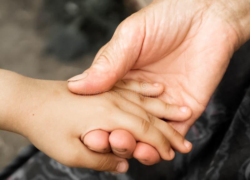 Mani di una bambina e di una nonna anziana Mani dei bambini che tengono uomo anziano, concetto di giorno di gentilezza del mondo fotografia stock libera da diritti
