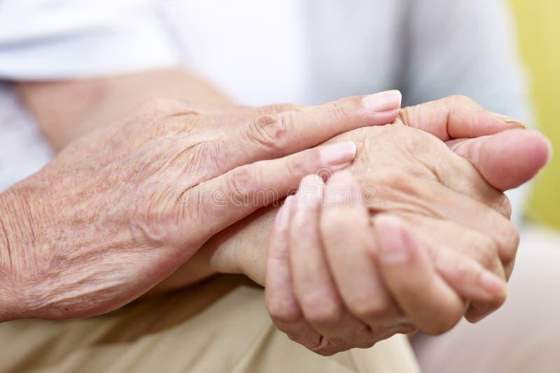 Mani di una coppia senior tenuta insieme immagine stock