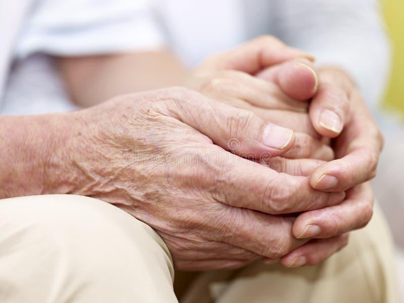 Mani di una coppia senior tenuta insieme fotografia stock