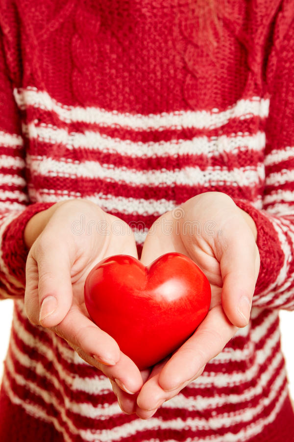Mani di una donna che tiene un cuore rosso di amore fotografie stock