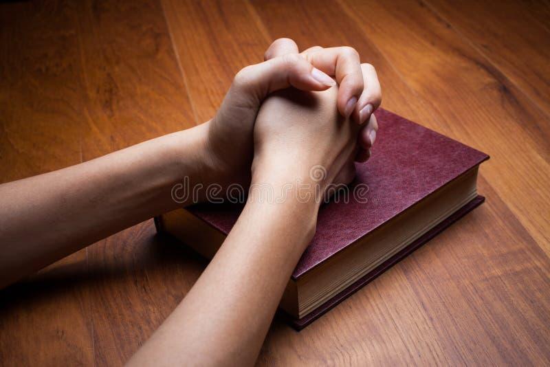 Mani di una donna su una bibbia immagini stock libere da diritti