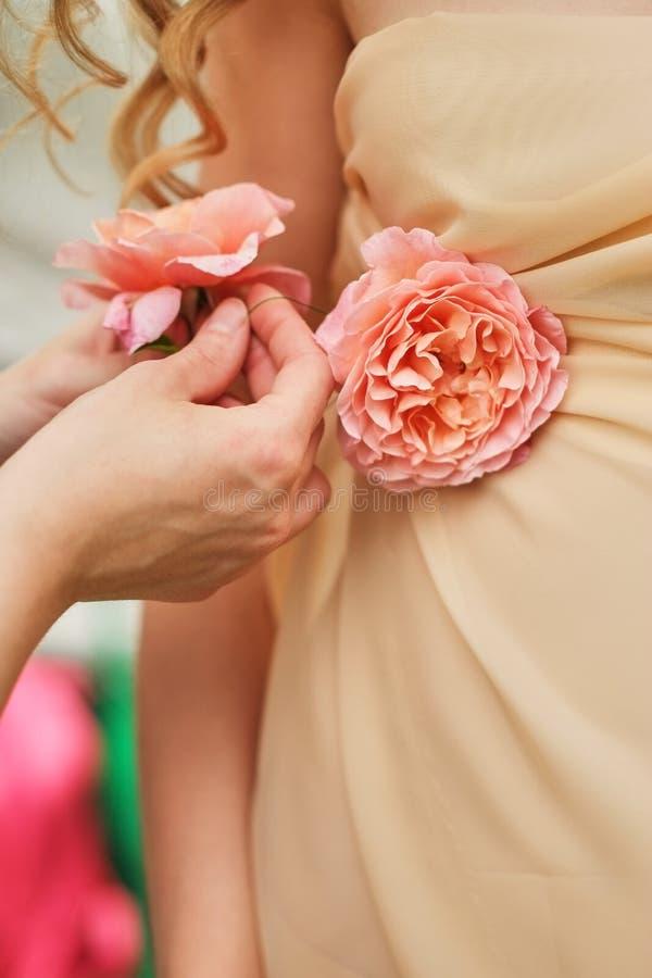 mani di una ragazza che corregge i fiori, rose, su un vestito da sposa, primo piano fotografie stock libere da diritti