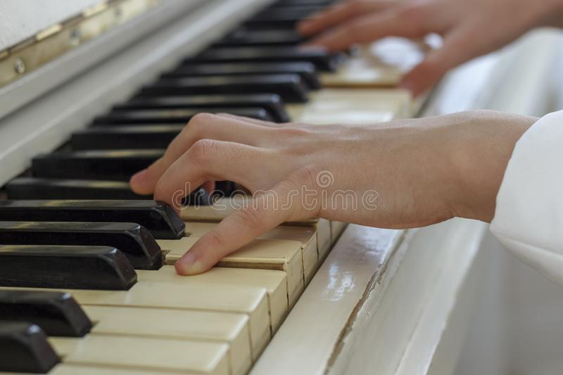 Mani di una ragazza che gioca su un piano bianco, primo piano immagini stock libere da diritti