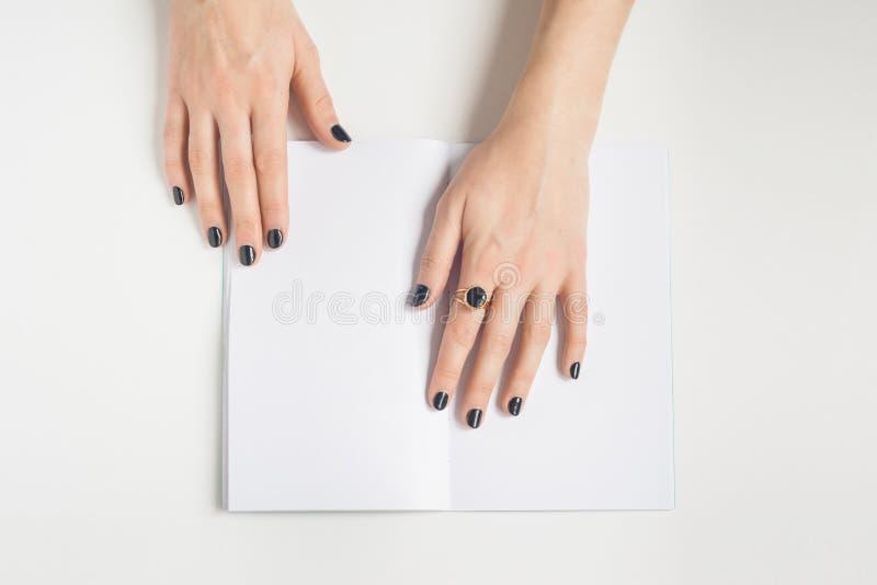 Mani di una ragazza con un manicure nero e un anello sulla sua maniglia un taccuino in bianco aperto su una tavola bianca immagini stock libere da diritti