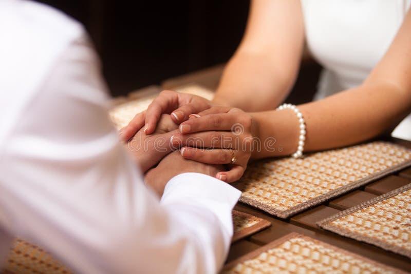 Mani di una seduta amorosa delle coppie immagini stock