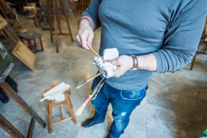 Mani di una tenuta e di una pulizia dell'uomo il suo spazzole immagine stock libera da diritti