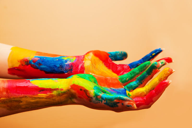 Mani dipinte, divertimento variopinto. Fondo arancio immagini stock