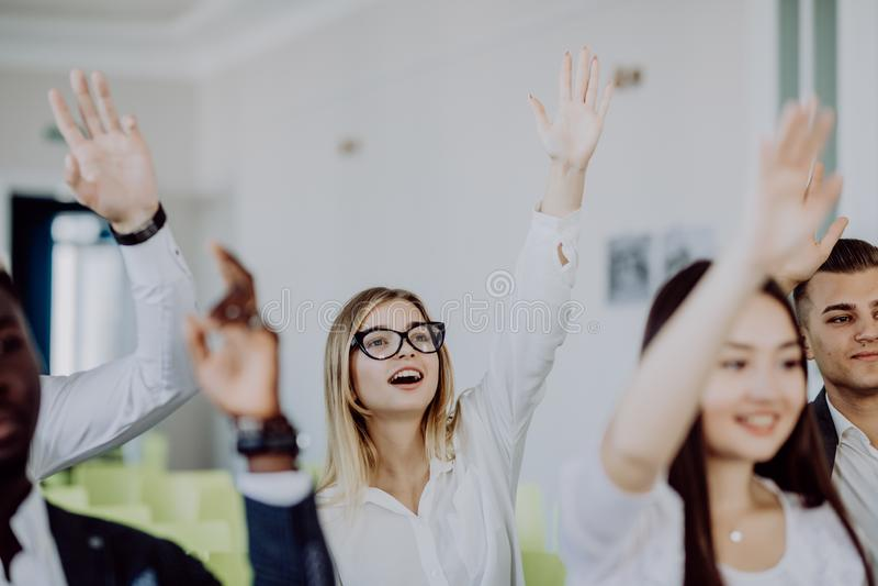 Mani e braccia su sollevati di grande gruppo nella stanza di classe di seminario essere d'accordo con l'altoparlante alla sala ri immagine stock libera da diritti