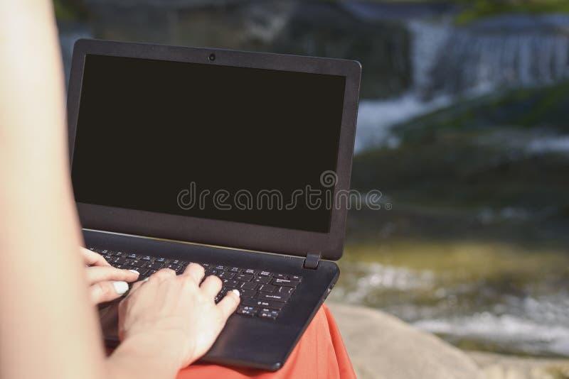 Mani e computer portatile femminili con uno schermo aperto sul rivestimento contro il contesto della cascata e del fiume Concetto fotografia stock