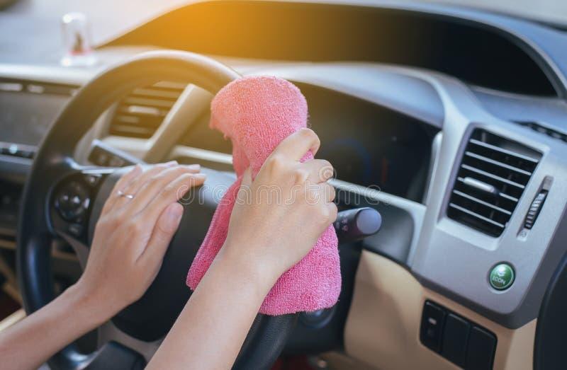Mani facendo uso del panno del microfiber con pulizia dentro la nuova automobile moderna fotografie stock libere da diritti