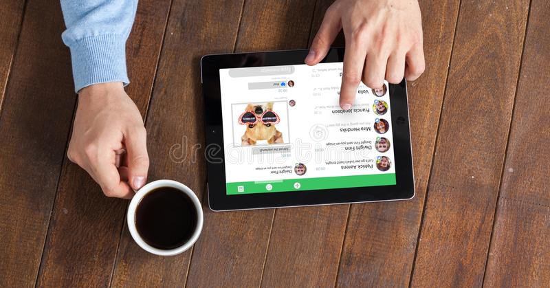 Mani facendo uso del PC della compressa mentre mangiando caffè fotografie stock libere da diritti