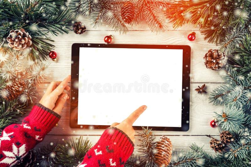 Mani facendo uso del pc della compressa sul fondo di Natale con i rami dell'abete, pigne, palle immagine stock libera da diritti