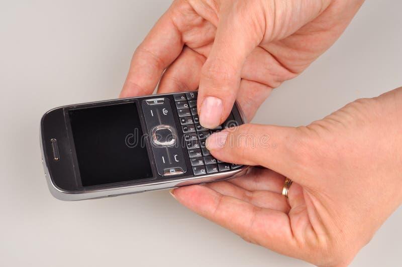 Mani facendo uso di un telefono cellulare di PDA, schermo in bianco delle donne fotografie stock