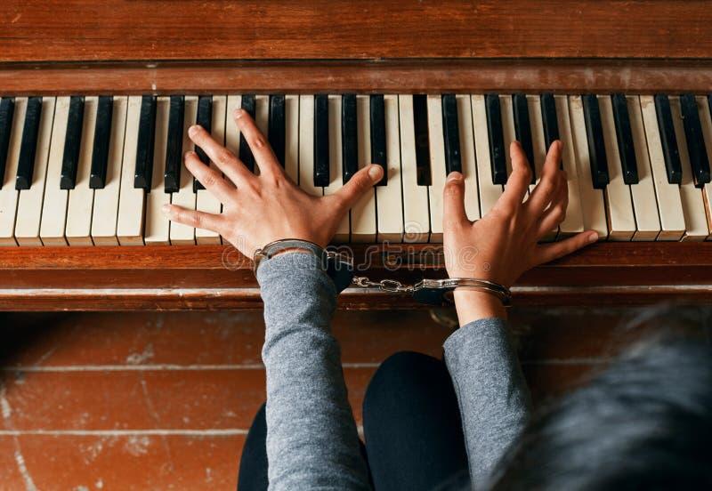 Mani femminili in catene su un piano immagine stock