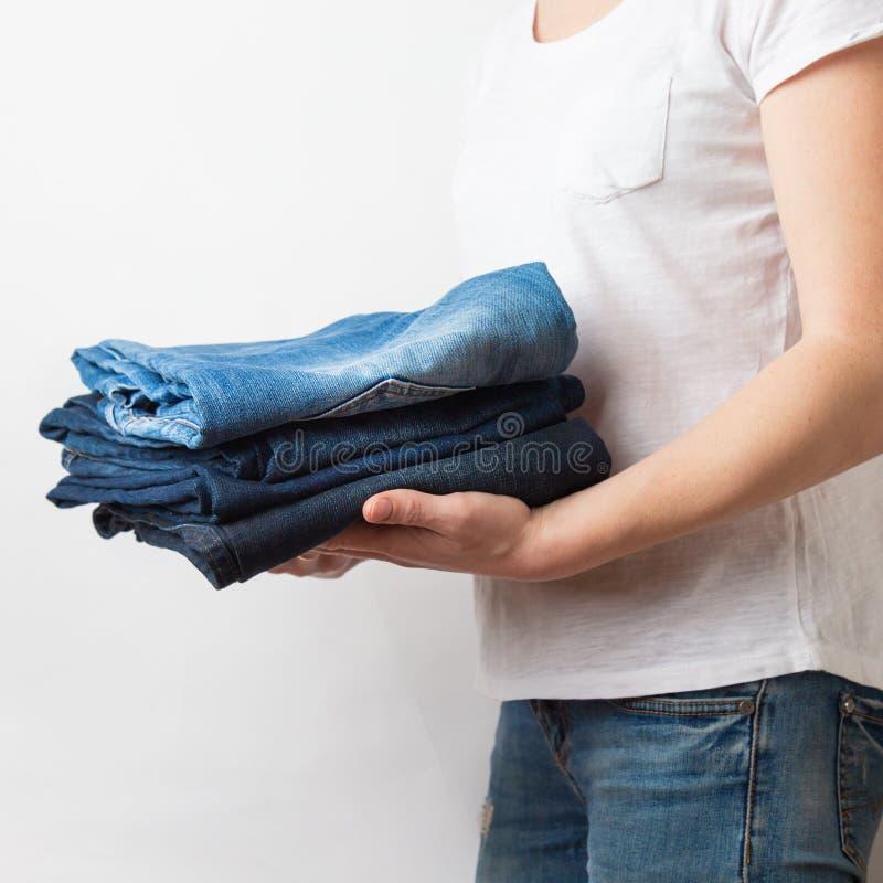 Mani femminili caucasiche del primo piano che tengono tre paia dei jeans blu del denim Isolato su priorità bassa bianca fotografia stock libera da diritti