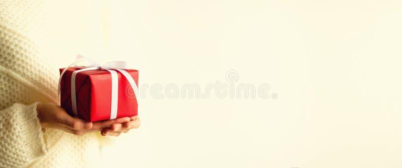 Mani femminili che aprono il contenitore di regalo rosso, spazio della copia Natale, nuovo anno, festa di compleanno, giorno del  fotografia stock libera da diritti