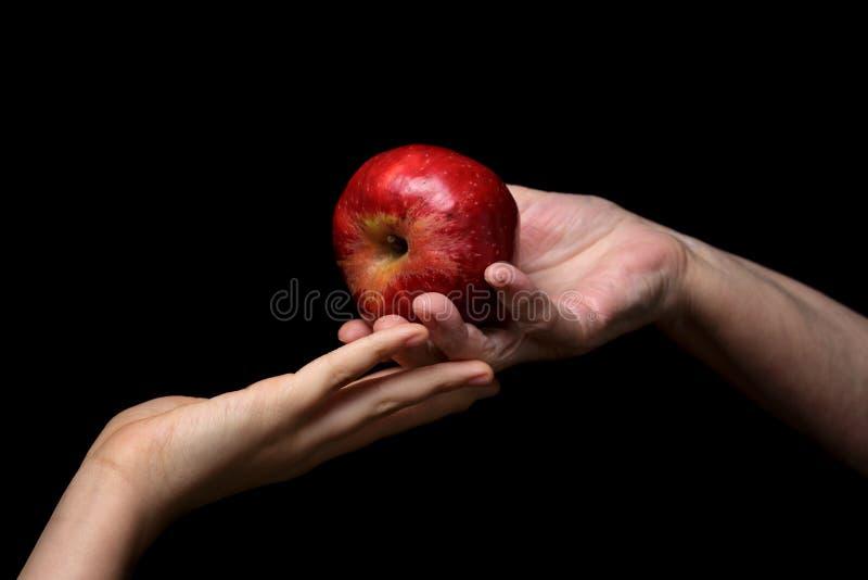 Mani femminili che danno mela immagini stock