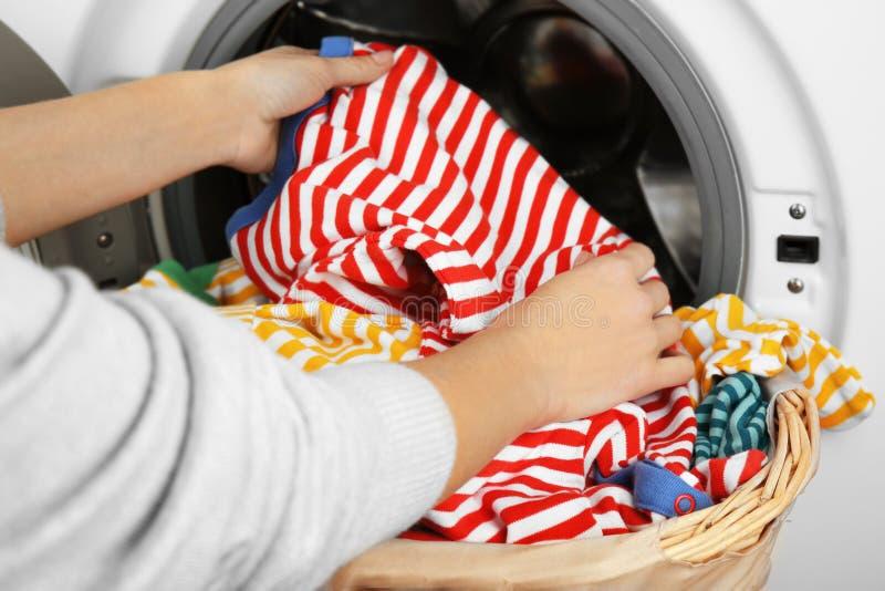 Mani femminili che escono i vestiti puliti fotografia stock