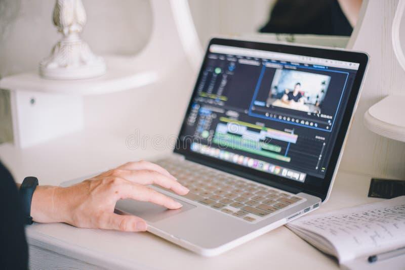 Mani femminili che lavorano ad un computer portatile in un video programma di editing immagini stock libere da diritti