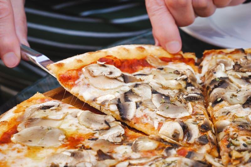 Mani femminili che prendono fetta di pizza del fungo fotografie stock libere da diritti